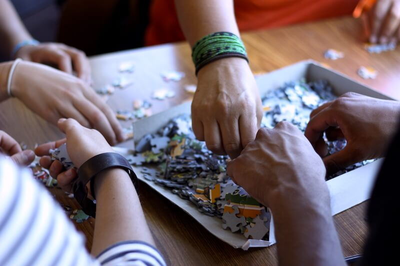 Honors students assembling a puzzle together
