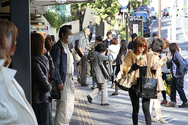 image: busy street scene in Tokyo featuring teens, shoppers, man wearing surgical mask