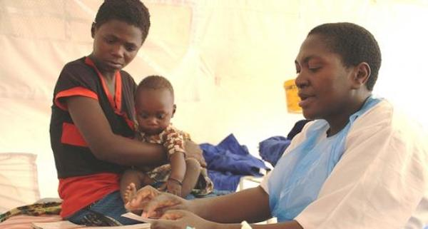 Image: community practitioner works with parent and child in medical tent