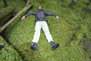 Tim on back, arms stretched, on bed of moss