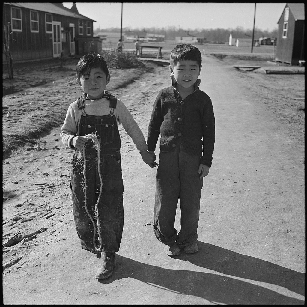 Two young Japanese children walking  down dirt road in an American Concentration Camp during WWII