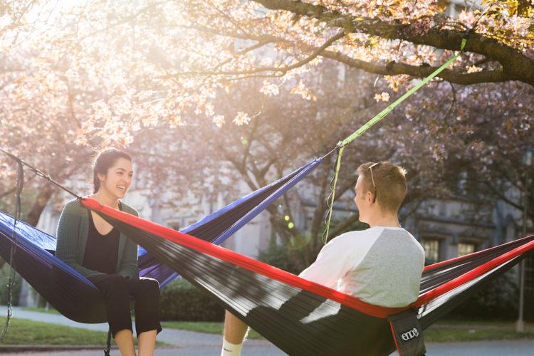 UW students enjoying the sun a on hammock at Rainier Vista.