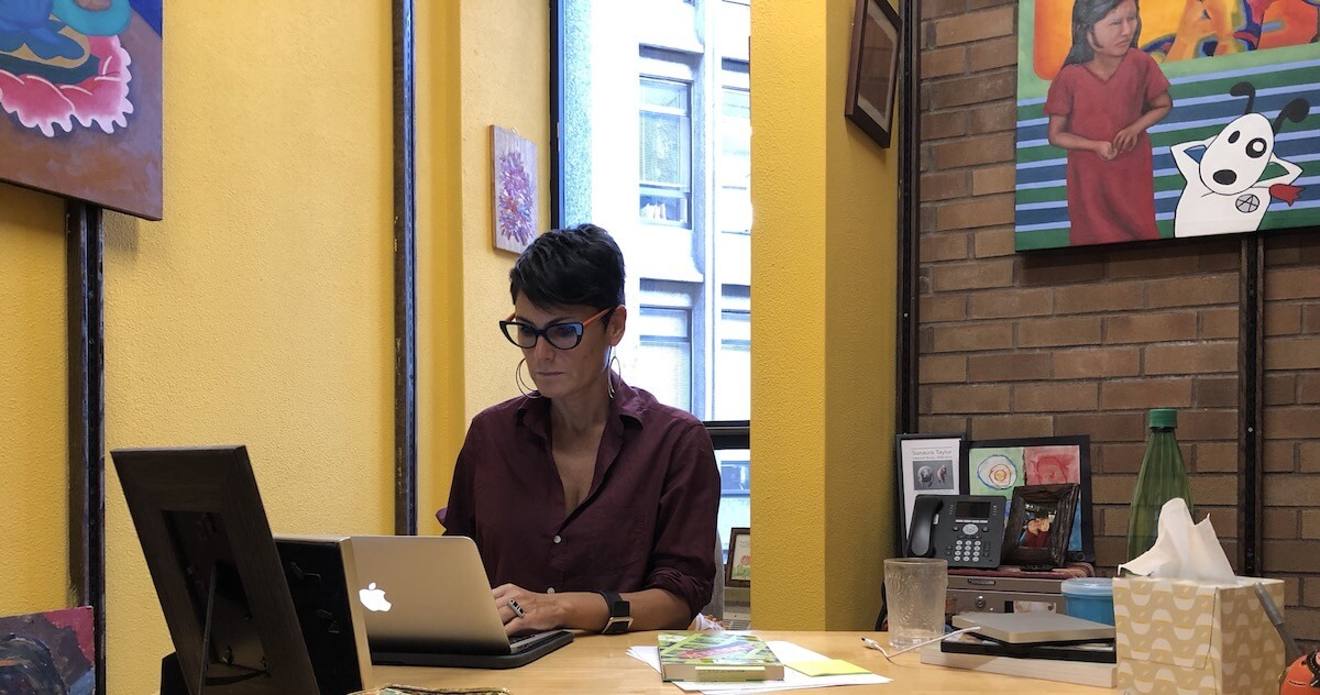 Dr. Garcia works on a laptop at her desk, surrounded by yellow walls and bright paintings.
