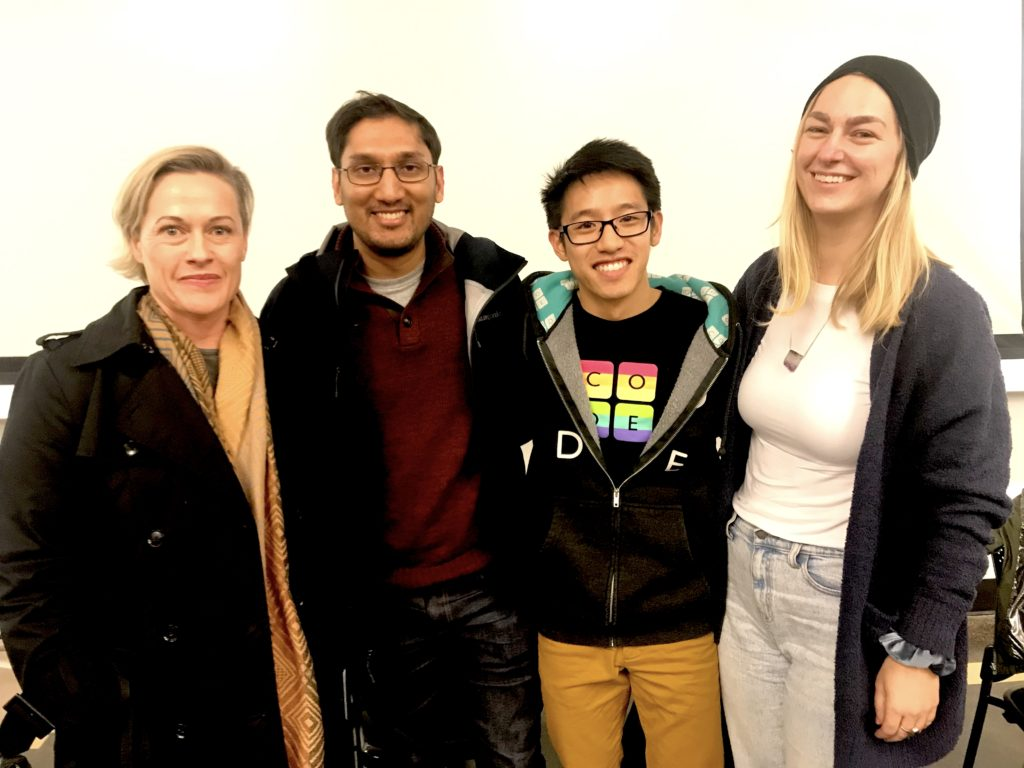 Alumni visitors to Honors 100 smiling together in a brightly lit classroom