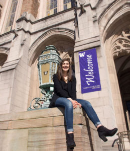 Reem Sabha sits on the steps of Suzzallo library on UW campus. She is smiling and it's a bright, sunny day.