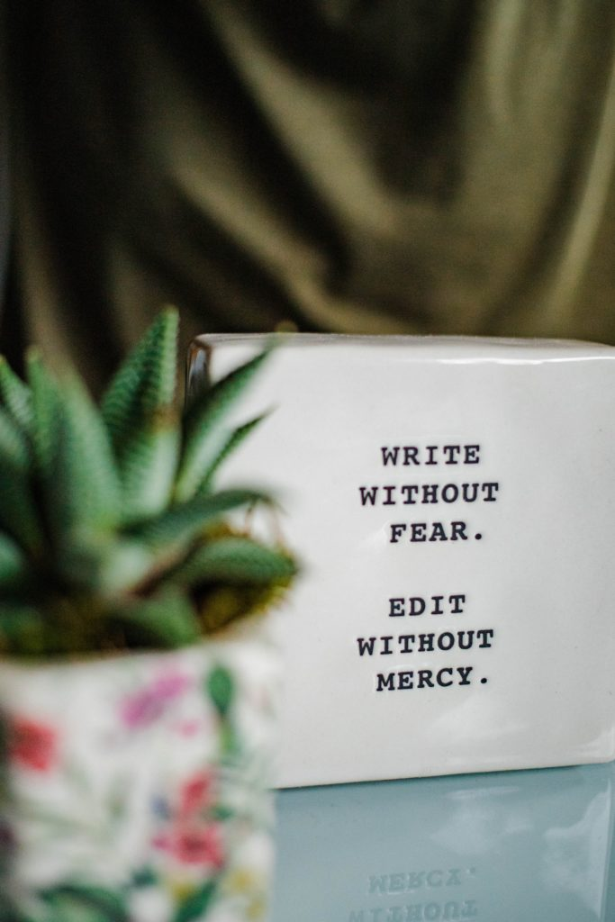 closeup of a block of glass on a desk that reads: Write without fear, edit without mercy