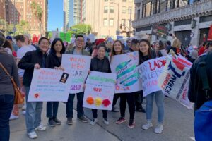 May and Sam Lim at LA Women's March, holding signs of support with their parents and sister.