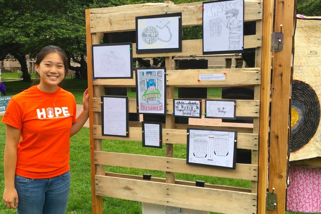May Lim in orange HOPE T-shirt, standing next to art exhibit to raise awareness about mass incarceration issues, on UW Seattle Campus