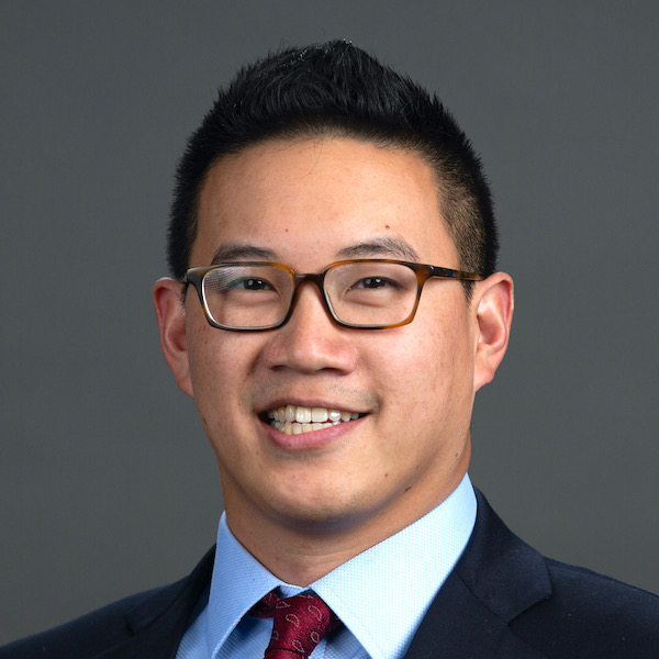 Headshot of Sam Lim smiling, in a suit and tie.