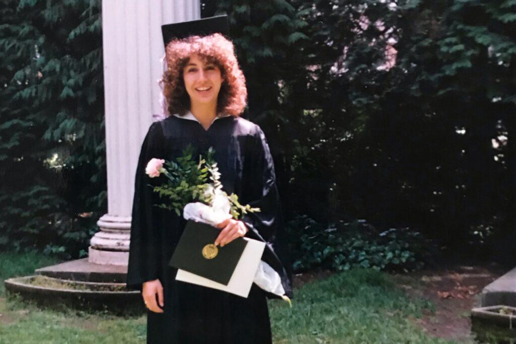 Juliana Villegas in cap & gown with flowers in UW's Sylvan Grove